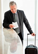 Businessman reading ticket at check in