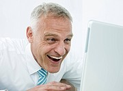 Businessman looking at laptop, laughing
