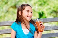 Smiling girl holding a bottle of juice