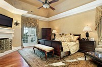 Master bedroom in elegant home with fireplace