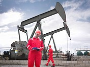 Workers with clipboard next to oil well
