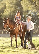 Senior man with dog assisting granddaughter 8_9 horseback riding in ranch