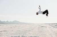 Young man doing backflip in desert