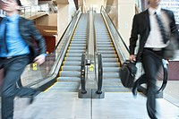 Rushing businessmen running off escalator