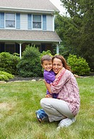 Hispanic mother hugging son in front yard