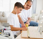 Hispanic father teaching his son carpentry