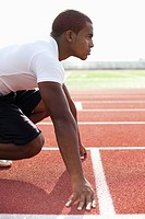 Black athlete crouching at track starting line (thumbnail)