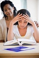 Mother comforting frustrated daughter doing homework
