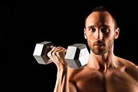 Head and shoulders of man lifting a weight, black background