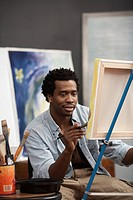 Black artist painting on easel