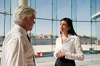 Business people talking in office lobby with glass wall