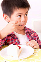 Young boy eating cake
