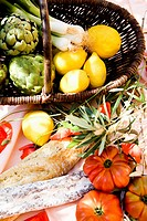 Basket with artichokes, lemons, sausage and tomatoes