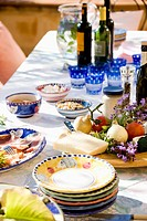 Plates, wine and fresh cheese and vegetables on table