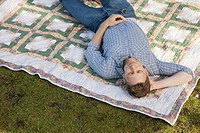 Man lying on a blanket in a park