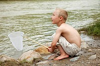 Little boy fishing in a stream
