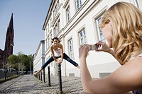 Young woman photographing friend jumping (thumbnail)