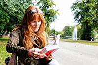 Woman reading a book in Cannon Hill Park, Edgbaston, Birmingham, West Midlands, England, UK