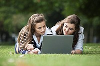 Students using laptop in grass