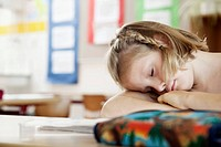 Girl resting on desk in classroom
