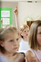 Girl raising hands in classroom
