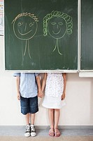 Schoolchildren and blackboard with smiley faces