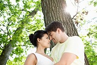 Young couple sitting beneath a tree