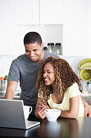 Young couple using a laptop while having breakfast (thumbnail)