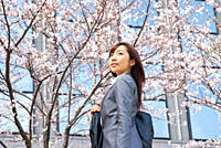 Young woman standing under cherry blossom tree