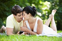 Young couple sharing an MP3 player in a park