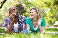 Young couple blowing bubbles in a park