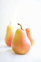 Three pears, one in focus in the foreground