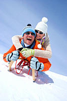 Smiling couple riding through snow on sled together