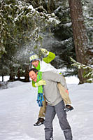 Man giving wife a piggyback in snowy woods