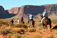 Rear view of horseback riders among the red rock of Monument Valley, Utah, Arizona.