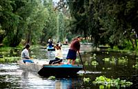 Residents ride in a boat through the water canals of Xochimilco on the south side of Mexico City. The water canals and gardens in Xochimilco was once ...