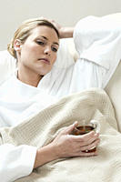 South Africa, Cape Town, Sick young woman lying in bed with tea