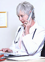 USA, California, Fairfax, Female doctor talking on phone and typing on keyboard