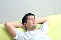 Russia, Voronezh, Pensive young man reclining on sofa