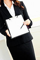 Close_up of an assertive businesswoman taking notes on her clipboard against a white background