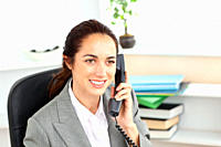 Attractive businesswoman talking on phone sitting in her office at her desk