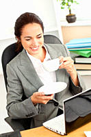 Smiling businesswoman holding a coffee while using a laptop at work in her office