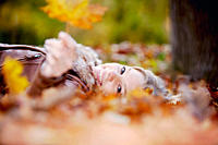 teenage girl lying on ground in autumn holding leaf
