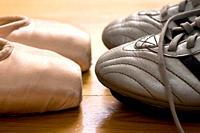 still life of ballet shoes and football boots