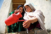 Afghan girls help each other to wash hands, using water they have collected from a nearby stream, on the steps of the latrine, at Bam Sarai School, in...