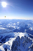 Hot_air balloon flying above Dolomites with Langkofel and Plattkofel in foreground, Sella range, Marmolada range and Pala range in background, aerial ...