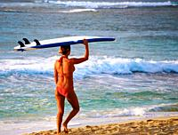 Girl carries surfboard on beach, Hawaii, USA