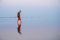Reflection of woman walking in Wadden sea, Juist, Germany