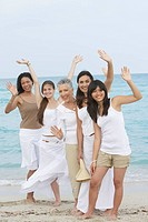 Diverse women standing on beach together waving