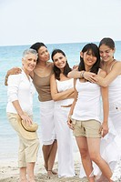 Diverse women standing on beach together